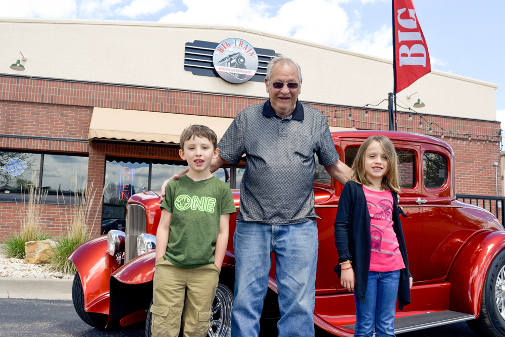 A classic car enthusiast with greets two children in front of Big Train.